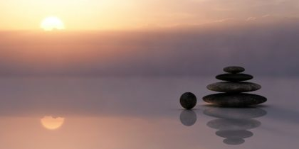 calm lake at sunset with stones