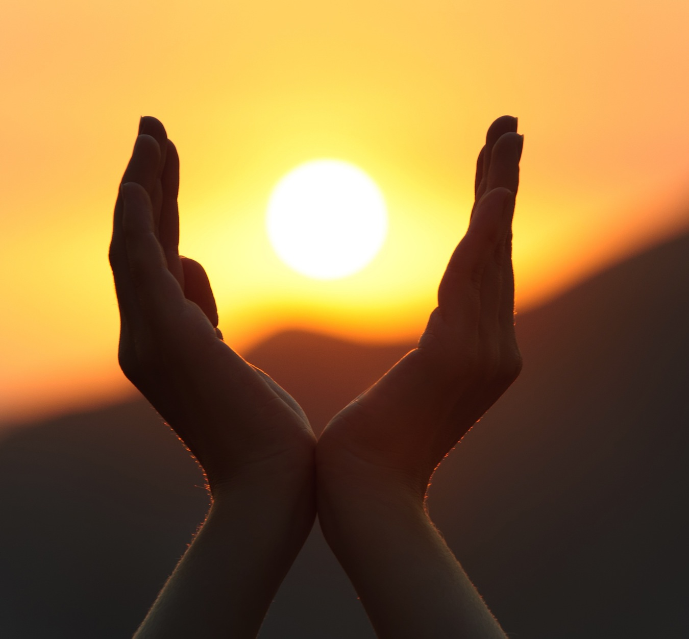 Setting sun in between two hands