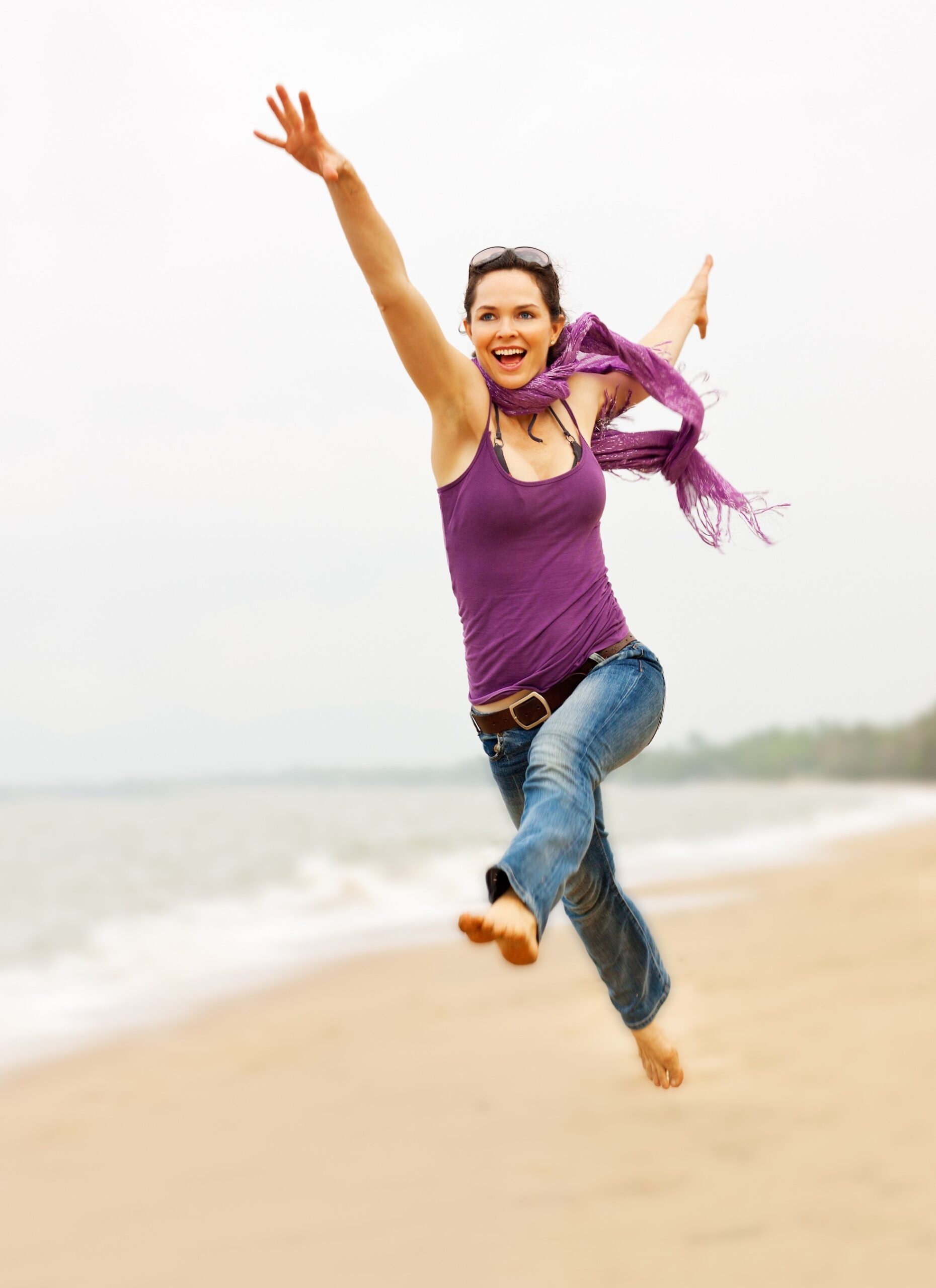 Woman running and leaping on beach